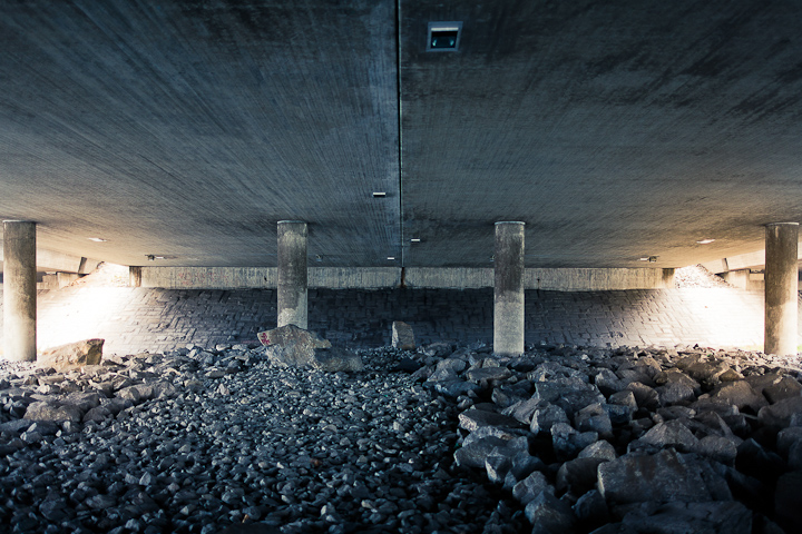 Under a bridge at the Västberga roundabout. Symmetry, concrete column, rocks. Light, dark.