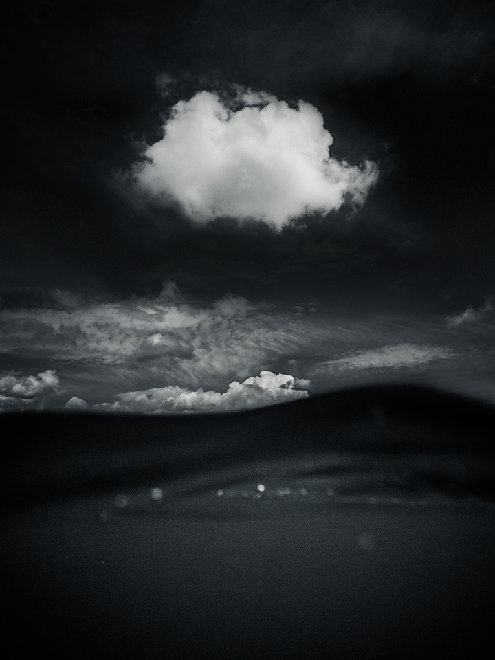 Suface by John Andreas Olsson. Canon S100, Ikelite 6242.10. Black and white, Sea and lonely cloud. Below, above, under, over.